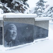 A wall-like memorial showing Dr. Martin Luther King's face looking to the right, in the snow.